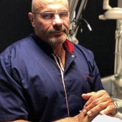Dr Krzysztof Łuksza pozujący do zdjęcia, w tle białe urządzenie
